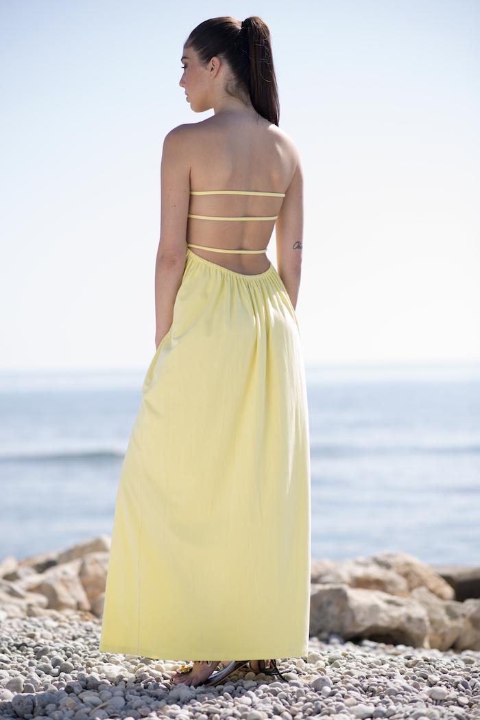 Vestido amarillo de algodón largo vaporoso hasta los pies, escote recto por delante con nido de abeja y escote profundo de espalda, con tres tiras para sujetar el pecho sin necesidad de llevar sujetador. Es un vestido práctico, sensual y cómodo para los días calurosos de verano.